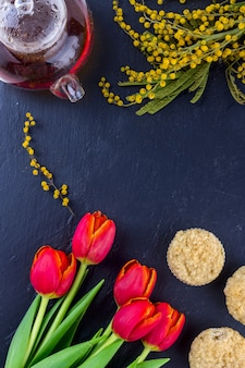 Women's day greeting card with tulips, mimosa, tea and cupcakes on black stone board background.
