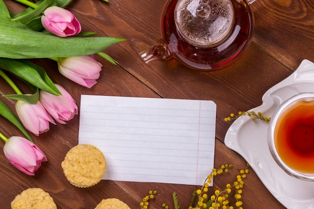 Women's day greeting card with tulips, mimosa, tea and cupcakes on brown wooden background.
