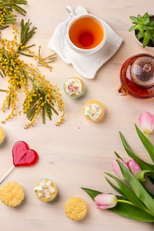 Women's day greeting card with tulips, mimosa, tea and cupcakes on wooden background.