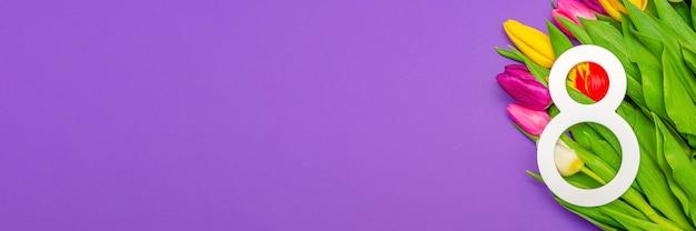 세계 여성의 날인 3월 8일 여성의 날. 보라색 배경에 튤립, 텍스트에 대 한 장소. 광고, 엽서, 축하에 적합합니다.