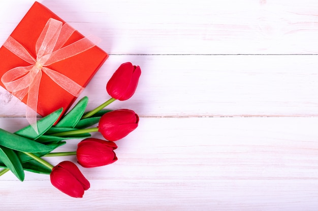 Women's day, mother's day, valentine's day concept red tulips bouquet and a gift
