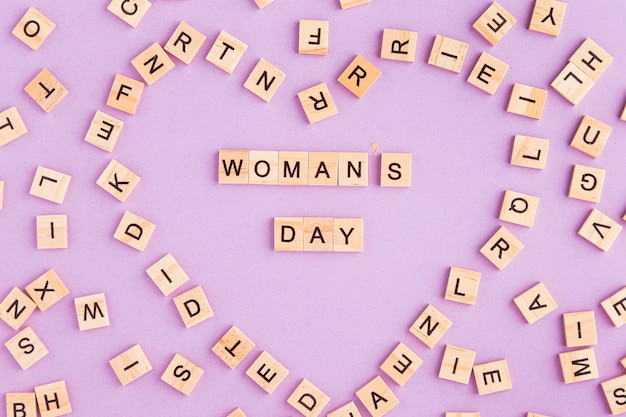 Women's day written in scrabble letters forming a heart shape