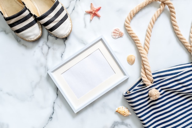 Women's desk with striped sandals, beach bag, seashells and blank picture frame.