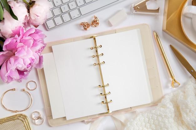 Женский дневник и золотые канцелярские товары. букет из розовых пионов. очки, белая клавиатура, ручка, ножницы и кофе на рабочем столе.
