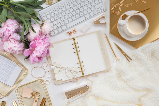 Women's diary and golden stationery. bouquet of pink peonies. glasses, a white keyboard, pen, scissors and coffee on the desktop.