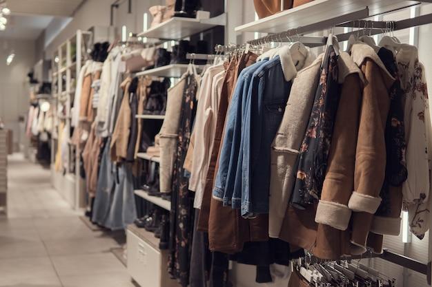 小売店のハンガーに女性のドレスとジャケット。ファッションとショッピングのコンセプト