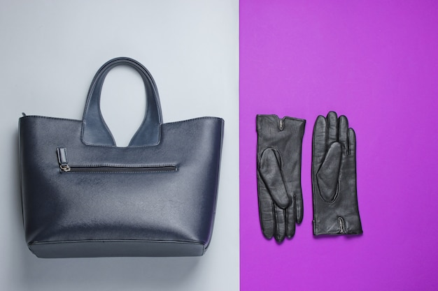 Women's fashion accessories on a gray-purple table. leather bag, gloves. top view