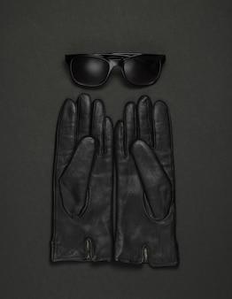 黒の背景に女性のファッションアクセサリー。革手袋、サングラス。上面図
