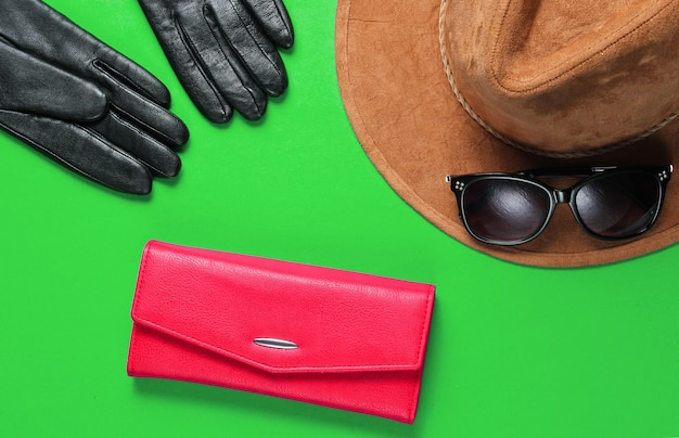 Women's fashion accessories. red leather wallet, sunglasses, gloves close-up on green background
