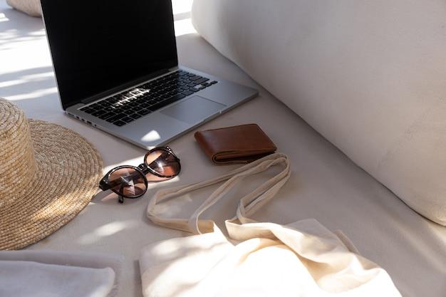 女性のファッションアクセサリー。スタイリッシュな女性のサングラス、麦わら帽子、買い物袋、枕と白いラウンジソファの上のラップトップ