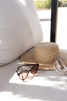 여성 패션 액세서리. 세련된 여성 선글라스, 밀짚 모자, 베개가 달린 흰색 라운지 소파에 쇼핑 가방