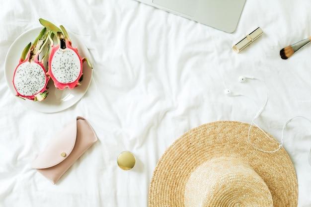 ノートパソコンと白いリネンでベッドに横たわっているエキゾチックなドラゴンフルーツの女性のファッションアクセサリー