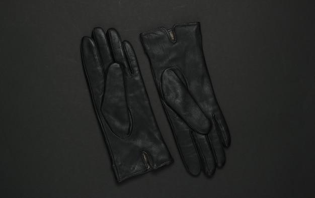黒の背景に女性のファッションの革手袋。上面図
