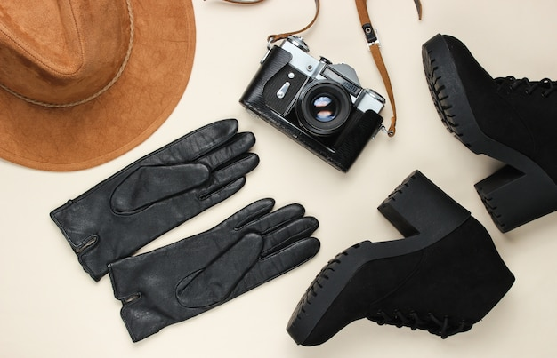 女性のファッショナブルな秋のアクセサリー、靴、ベージュのフラットレイアウトのレトロなフィルムカメラ