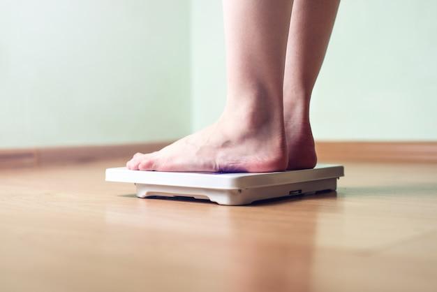女性の足は体重管理のために機械式体重計に乗っています