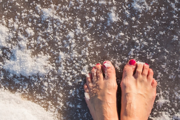 Женские ноги босиком без обуви на замерзшем озере, лед в снежинках