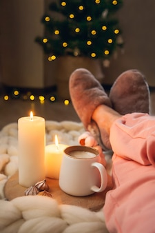 Women's feet in home fur slippers, cup of cappuccino, candles on blanket of thick yarn and christmas tree with lights. the atmosphere of homeliness and comfort