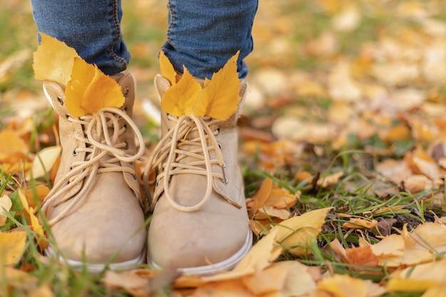 秋の茶色の靴と秋の黄色の葉のブルージーンズの女性の足、秋のファッション、クローズアップ