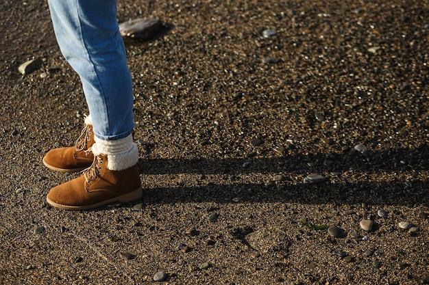 ビーチでジーンズと茶色のデミシーズンのスエードブーツの女性の足。強い日光。秋のパレット。