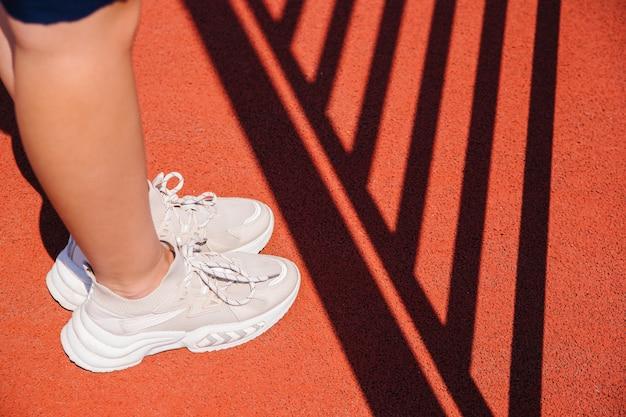 Женские ножки в спортивной обуви стоят на спортивном поле. красное покрытие из искусственного материала. на пол падают красивые тени от оборудования. концепция занятий спортом.