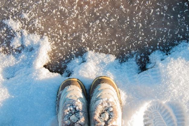 Женские ножки в винтажных белых сапогах на замерзшем озере