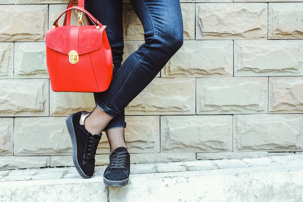 Women's feet near brick wall with red backpack in hands