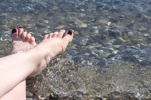 Women's feet on sea pebbles near the water in the shore.