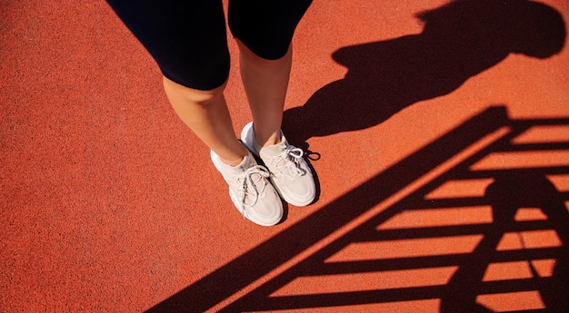 Women's feet in sports shoes are standing on the sports field. red coating made of artificial material. beautiful shadows from the equipment fall on the floor. the concept of playing sports.