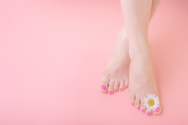 Women's feet with pedicure on nails and chamomile flower decoration. skincare concept