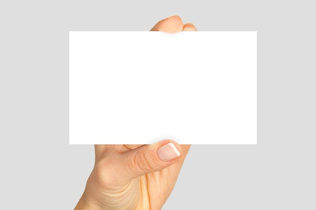 Women's fingers holding a blank business card isolated on gray