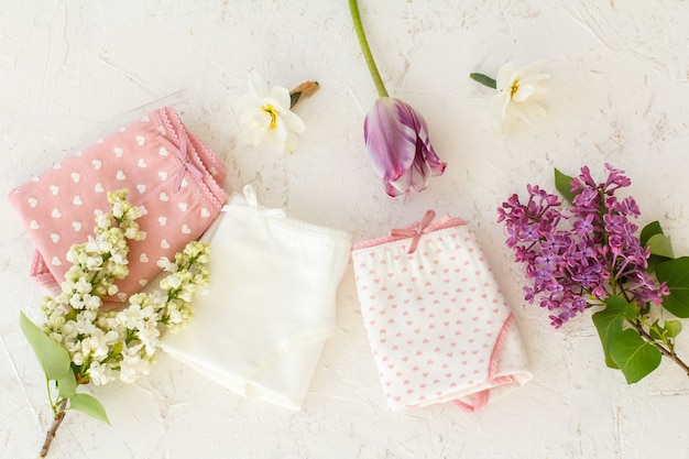 Women's folded cotton panties with buds of daffodil flowers, a tulip flowers and jasmine flowers on the white structured background. woman underwear set. top view.