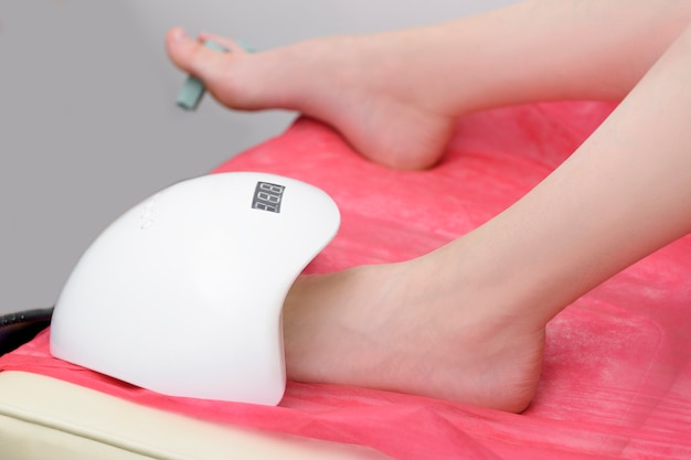 Women's foot in a lamp for drying nail polish