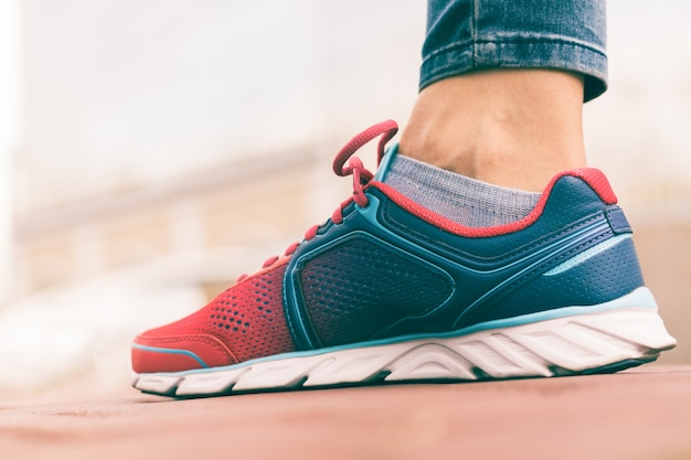 Women's foot in red and blue sneaker close-up, low angle shooting