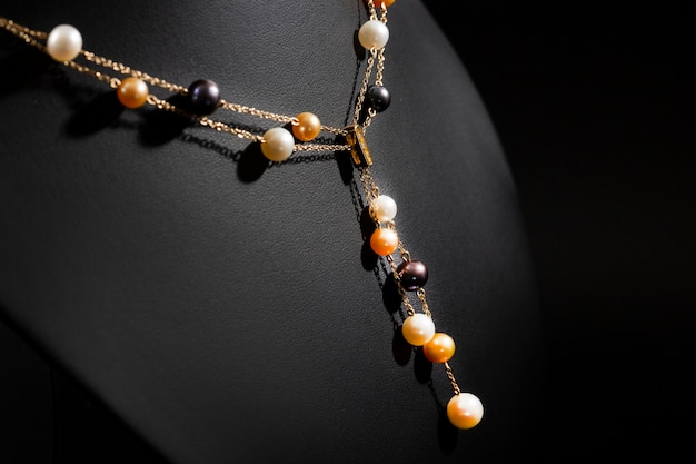 Women's gold necklace made of chains and pearls on a black stand. close-up