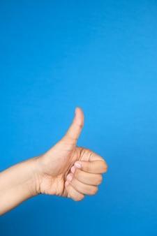 Женская рука рука показывает палец вверх на синем фоне