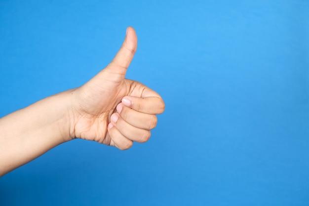 青いスペースに親指を立てる女性の手の手