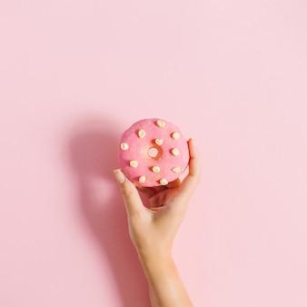 Женская рука держит пончик на розовом