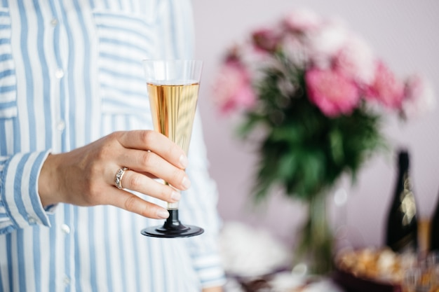 Women's hand holding a glass of champagne on the background of the festive table