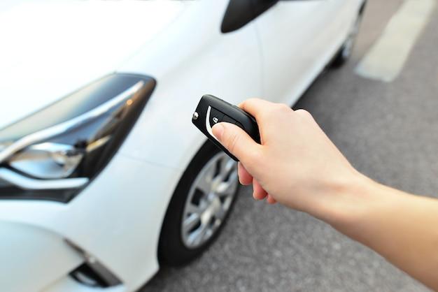 リモコンの女性の手で押すと、車のドアの警報システムのロックが解除されます