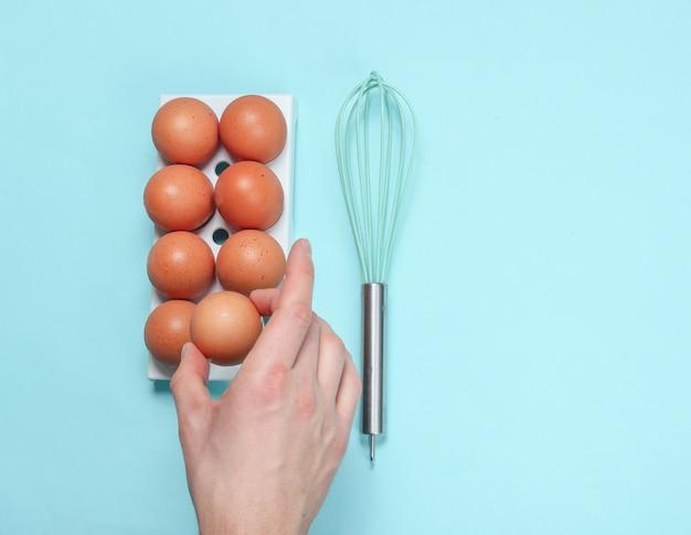 Women's hand taking hen's egg from eggs tray on blue.