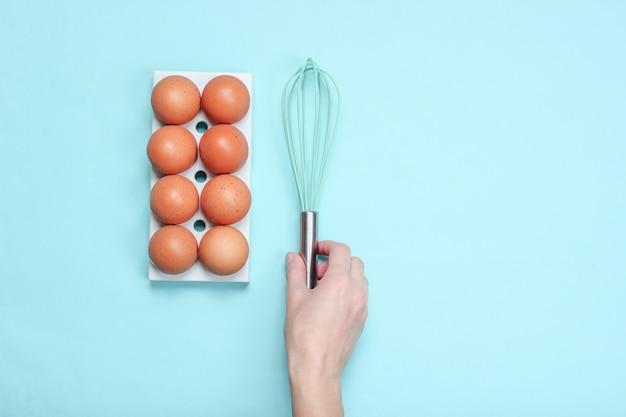 Women's hand taking whisk, eggs tray on blue.