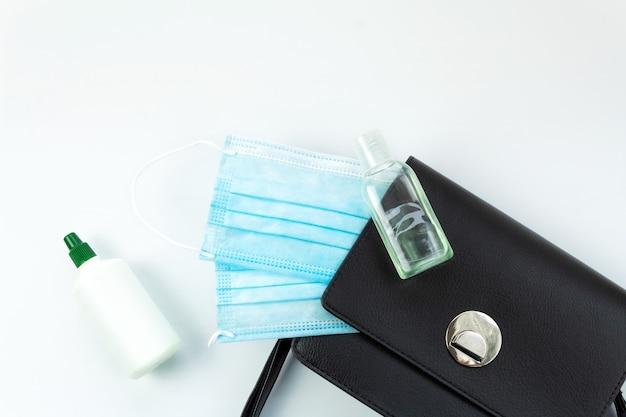 不可欠なもの、防腐剤、医療マスク、白い背景、上面図、黒い財布が付いている女性のハンドバッグ