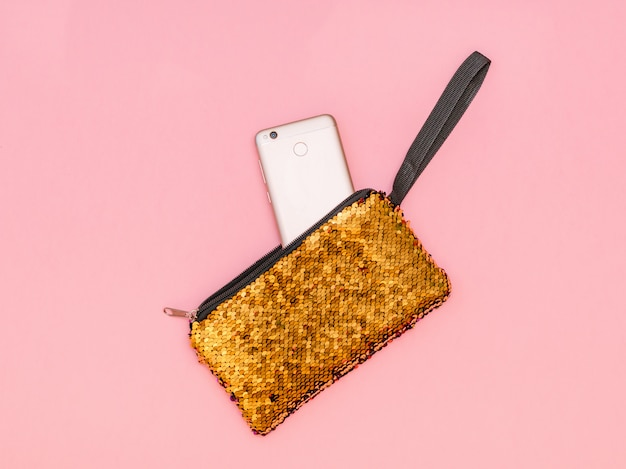 Women's handbag with a sticking phone of gold color on a pink table. pastel color. flat lay.