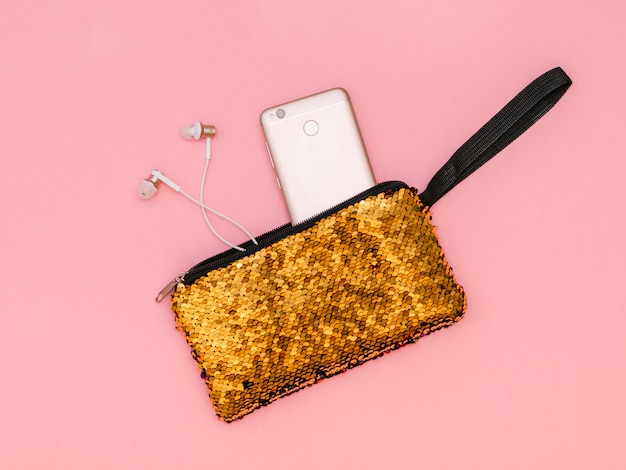Women's handbag with a sticking phone and headphones of gold color on a pink table.