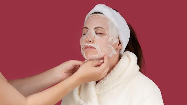 여성의 손은 테리 드레싱 가운을 입은 젊은 여성의 얼굴에 화장품 패브릭 마스크를 조정합니다.