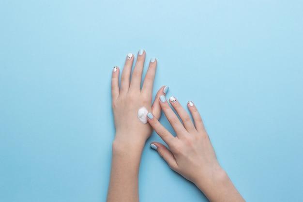 Женские руки наносят крем для увлажнения рук.