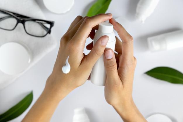 Женские руки наносят косметический увлажняющий крем-лосьон на белый стол