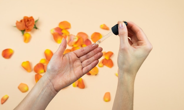 물방울과 장미 오일을 적용하는 여자의 손. 피부 관리 개념. 자연 의학.