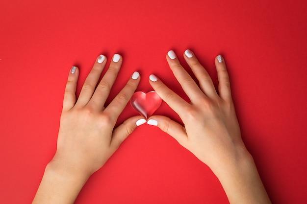 여성의 손이 빨간색 표면에 유리 심장을 움켜 쥐고 있습니다.