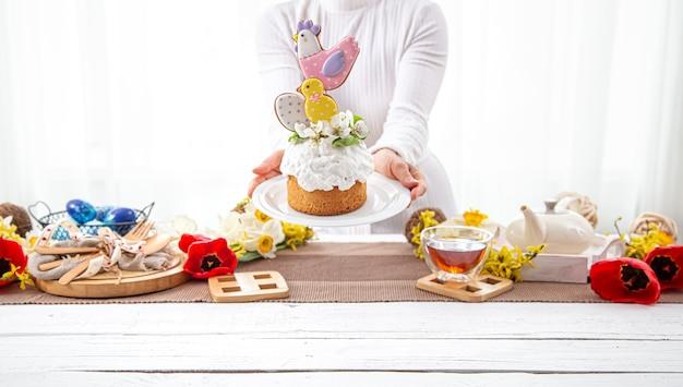 女性の手は、花と明るいディテールで飾られたお祝いのイースターケーキを持っています。イースター休暇の準備の概念。